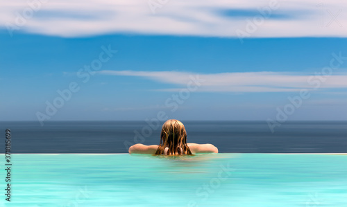 Foto Girl in the pool looking the sunrise, A slim girl with long hair stands and hat