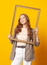 Portrait Of Woman With Empty Picture Art Frame Isolated On Yellow Background