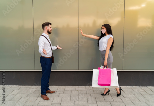 Fotomural Young woman doesnt allow man to approach her without face mask