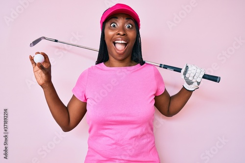 Valokuvatapetti African american golfer woman with braids holding golf ball celebrating crazy and amazed for success with open eyes screaming excited