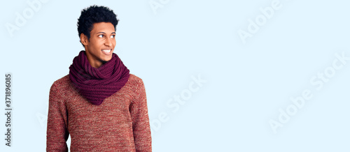 Young african american man wearing casual winter sweater and scarf looking away to side with smile on face, natural expression Canvas-taulu