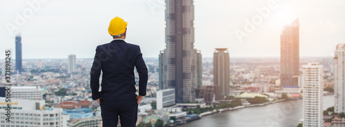 architect man wear black suit and yellow helmet view from back standing on building looking for cityscape Fototapete