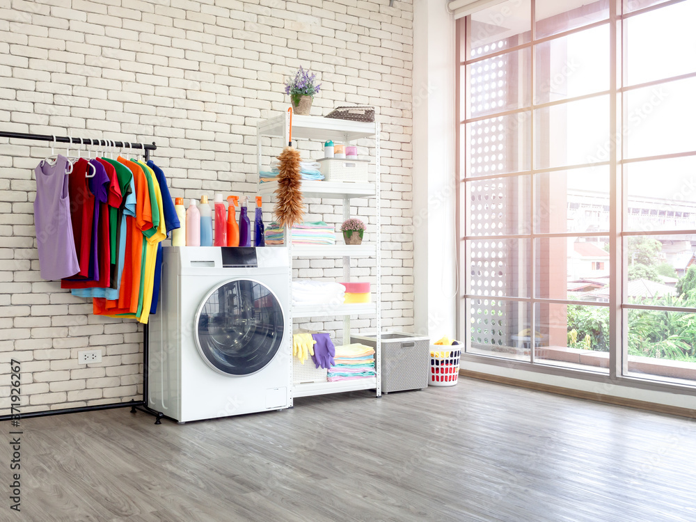 Fototapeta Laundry room interior with washing machine and colorful clothes on white vintage brick wall background.