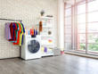 Laundry room interior with washing machine and colorful clothes on white vintage brick wall background.