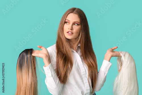 Fotografie, Obraz Beautiful young woman with different wigs on color background