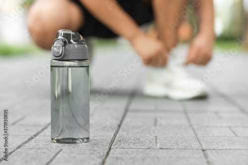 Fotomural Bottle of water and sporty man tying shoelaces in park