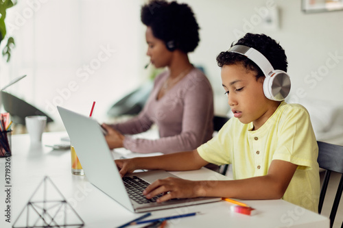 Fotografiet African American boy using laptop while his mother is working in the background