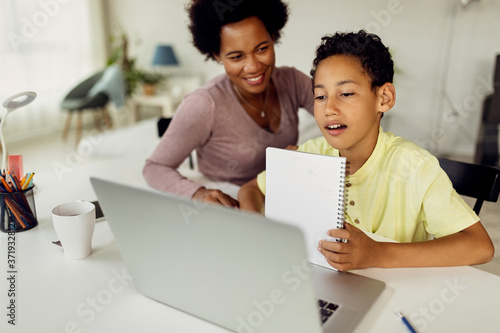 Fotografija Black boy making video call over laptop while homeschooling with his mother