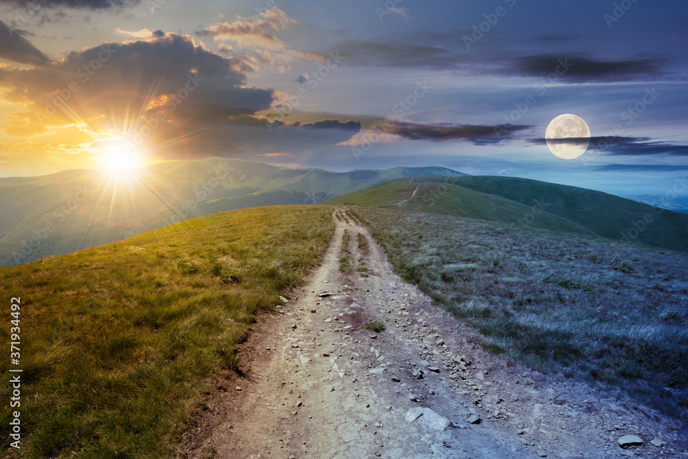 Fototapeta day and night time change concept above the mountain road through grassy meadow. wonderful summer adventure in twilight beneath a sky with sun and moon.
