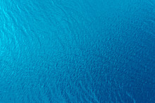 Aerial View Of A Crystal Clear Sea Water Texture. View From Above Natural Blue Background. Blue Water Reflection. Blue Ocean Wave. Summer Sea. Drone. Top View