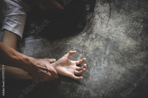Fotografía Close up  man hands holding a woman hands for rape and sexual abuse concept