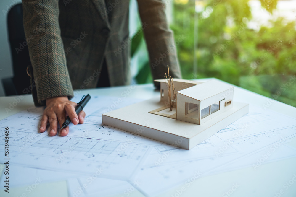 Fototapeta An architect working on an architecture house model with shop drawing paper in the office
