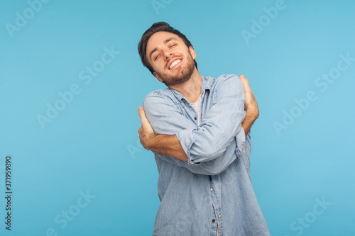I love myself! Portrait of selfish narcissistic man in worker denim shirt embracing himself and smiling with expression of great ego, pleasure and self-esteem фототапет