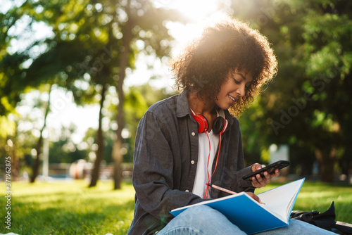 Fotografija Image of girl writing in exercise book while using cellphone