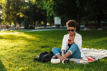 Woman Sitting On Grass In Park While Using Smartphone