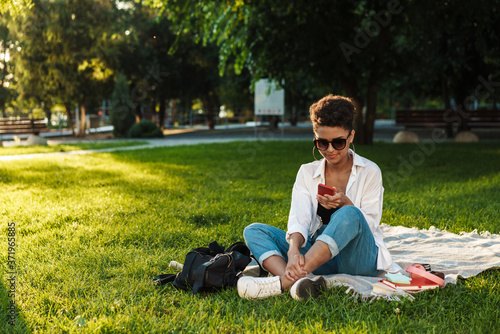 Photo Woman sitting on grass in park while using smartphone