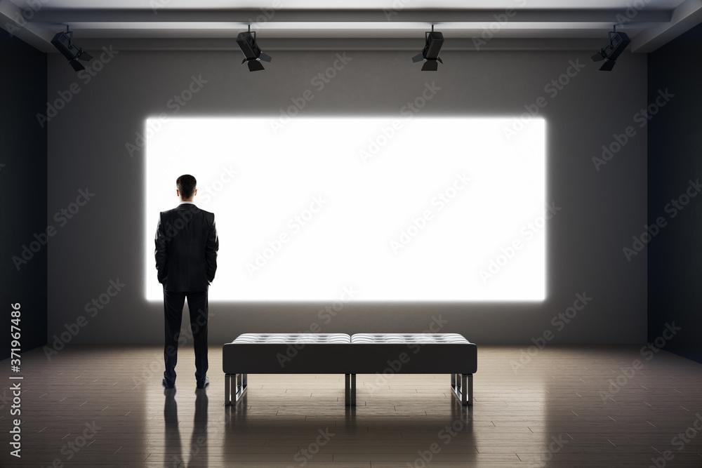 Fototapeta Businessman standing in exhibition interior