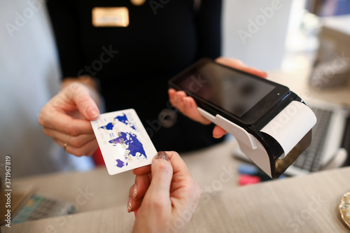 Fototapeta Client holds out credit card for payment terminal
