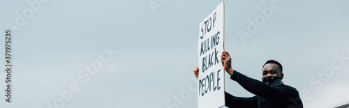 Fototapeta panoramic crop of african american man holding placard with stop killing black p