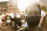 Young black man wearing face mask during equal rights protest - Concept of demonstrators on road for no racism campaign- Focus on eyes
