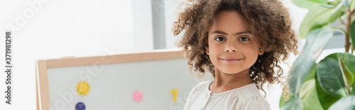 horizontal crop of curly african american child looking at camera Fototapet