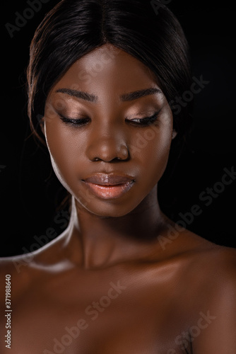 african american naked woman looking down isolated on black Fototapeta