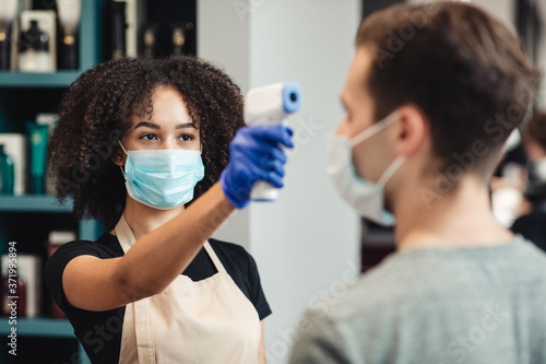 Black female hairdresser measuring body temperature to client