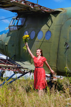 Young Woman In A Red Pin Up Dress Waves A Bunch Of Yellow Wildflowers At An Abandoned Airplane