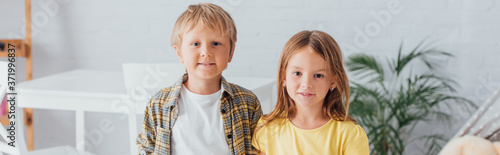 panoramic shot of brother and sister looking at camera while standing at home Canvas Print