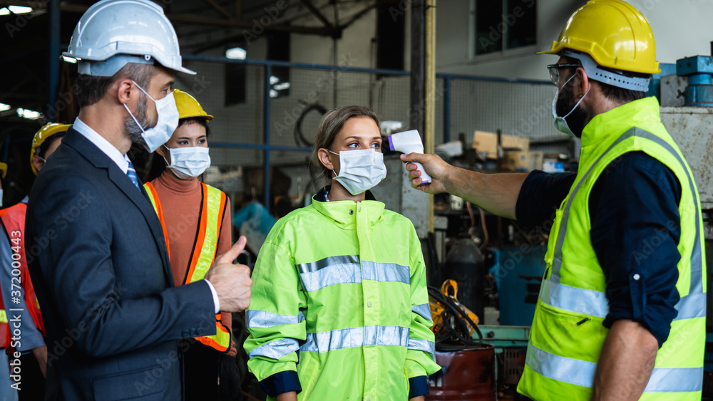 Fototapeta Industrial worker and engineer stand in line to check flu with infrared thermometer and manager show thumb up before enter to work and protect Coronavirus or Covid-19, safety and protection concept
