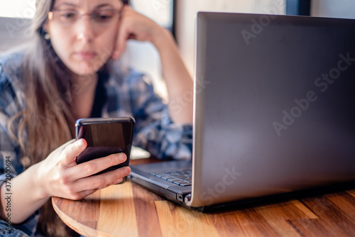 Sad woman checking smart phone Canvas Print