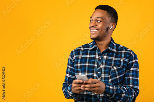 Happy African Guy With Smartphone Listening To Podcast, Studio Shot Wallpaper Mural