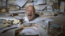 Stressed Businessman Buried Under A Lot Of Paperwork