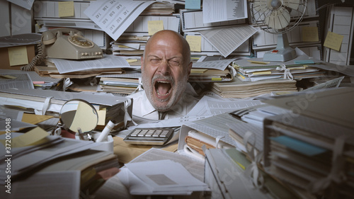 Stressed businessman buried under a lot of paperwork Wallpaper Mural