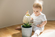 A One-year-old Baby Waters The Plant From A Small Watering Can On The Floor. Natural Motherhood, Easy Upbringing, Home Life With A Child, Child Development