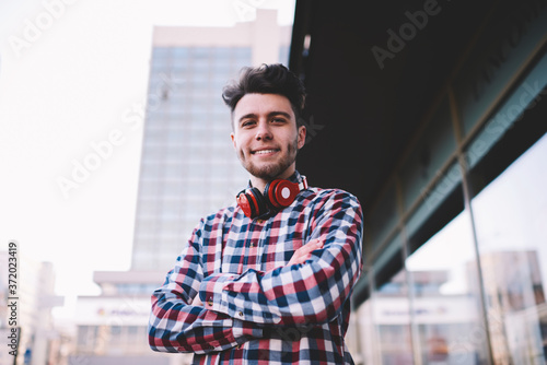 Fotografering Half length portrait of confident hipster guy standing with crossed arms outdoor