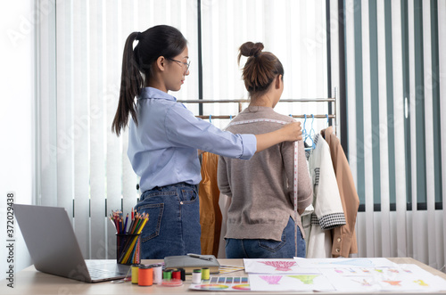 Foto Asian clothing designers are measuring customers' body sizes in preparation for tailoring in design rooms