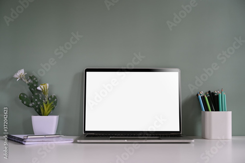 Fotomural Workspace mockup laptop, pencil, notebook and cactus on desk with green background