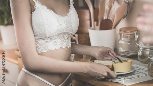 Foto Seductive asian girlfriend in her lingerie is preparing easy breakfast in wooden kitchen