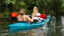 Zwei Mädchen In Einem Blauen Kanu