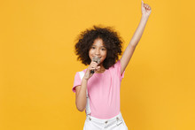 Funny Little African American Kid Girl 12-13 Years Old In Pink T-shirt Isolated On Yellow Wall Background Studio. Childhood Lifestyle Concept. Mock Up Copy Space. Sing Song In Microphone Rising Hand.
