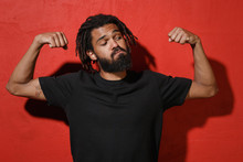 Strong Young African American Man Guy With Dreadlocks 20s In Black Casual T-shirt Posing Showing Biceps Muscles Spreading Hands Looking Aside Isolated On Bright Red Color Background Studio Portrait.