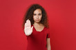 canvas print picture - Young african american woman girl in casual t-shirt posing isolated on red background studio portrait. People sincere emotions lifestyle concept. Mock up copy space. Showing stop gesture with palm.
