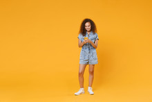 Full Length Portrait Of Smiling Young African American Woman Girl In Denim Clothes Isolated On Yellow Wall Background In Studio. People Lifestyle Concept. Using Mobile Cell Phone, Typing Sms Message.