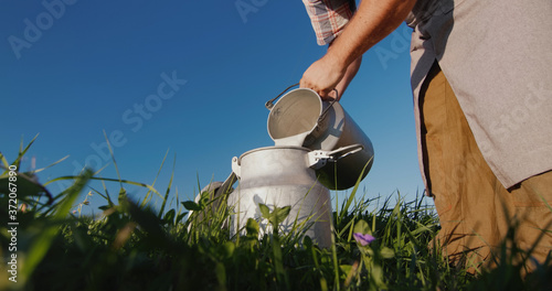 Photo The milkman pours milk into the can against the background of a green meadow