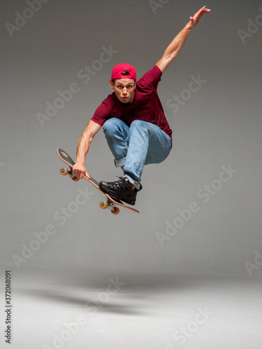 Cool young guy skateboarder jumps on skateboard in studio on gray background. Photography about skateboarding tricks