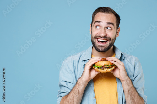 Obraz na plátně Excited young bearded man guy 20s wearing casual clothes posing holding in hands american classic fast food burger looking aside up isolated on pastel blue color wall background studio portrait