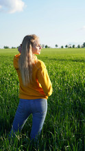 Portrait Of A Young Blonde Girl Makes A Selfie On The Phone Against The Background Of A Green Field. Blue-eyed Model On A Rapeseed And Wheat Field. Agriculture