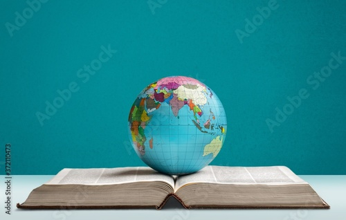 Foto Heavy book and globe of a planet on the desk