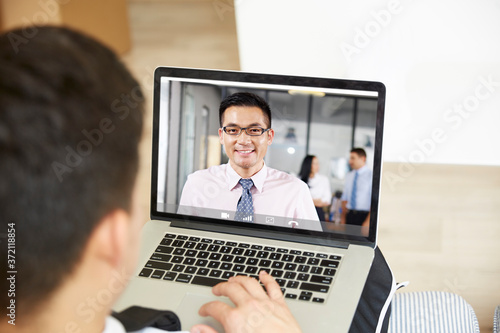 Fototapeta asian business man working from home meeting with colleague via video chat obraz na płótnie